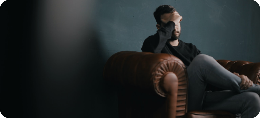man sitting on couch holding his head
