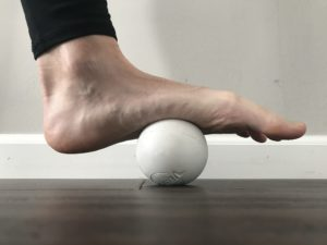 physical therapy stretch - rolling ball under arch of foot