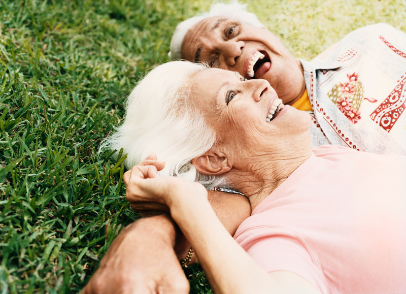 Senior Couple Lie on the Grass, Laughing