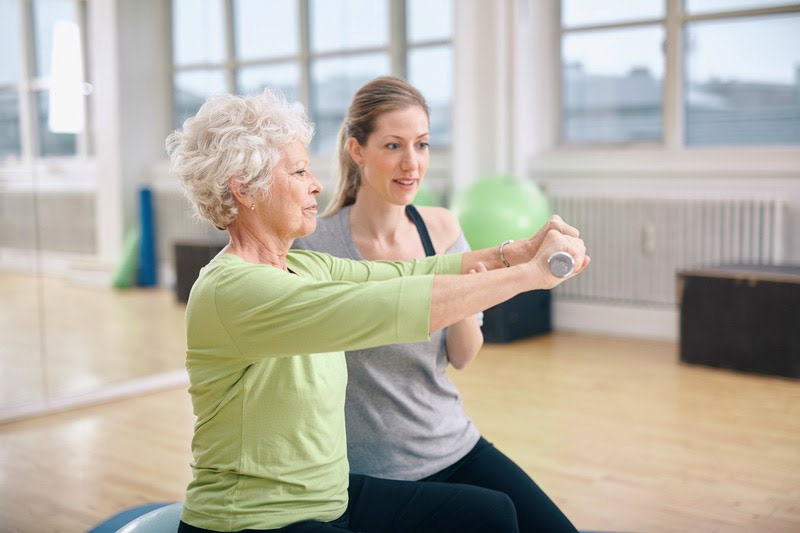 physical therapist working with patient doing yoga at fitness facility in st petersburg, florida