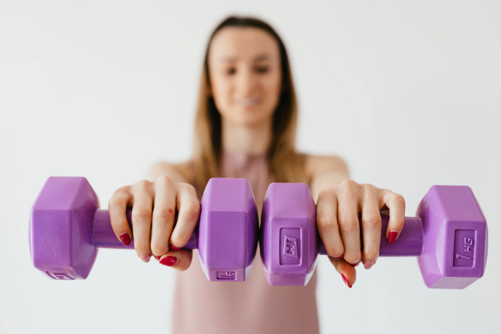 woman holding purple dumbells