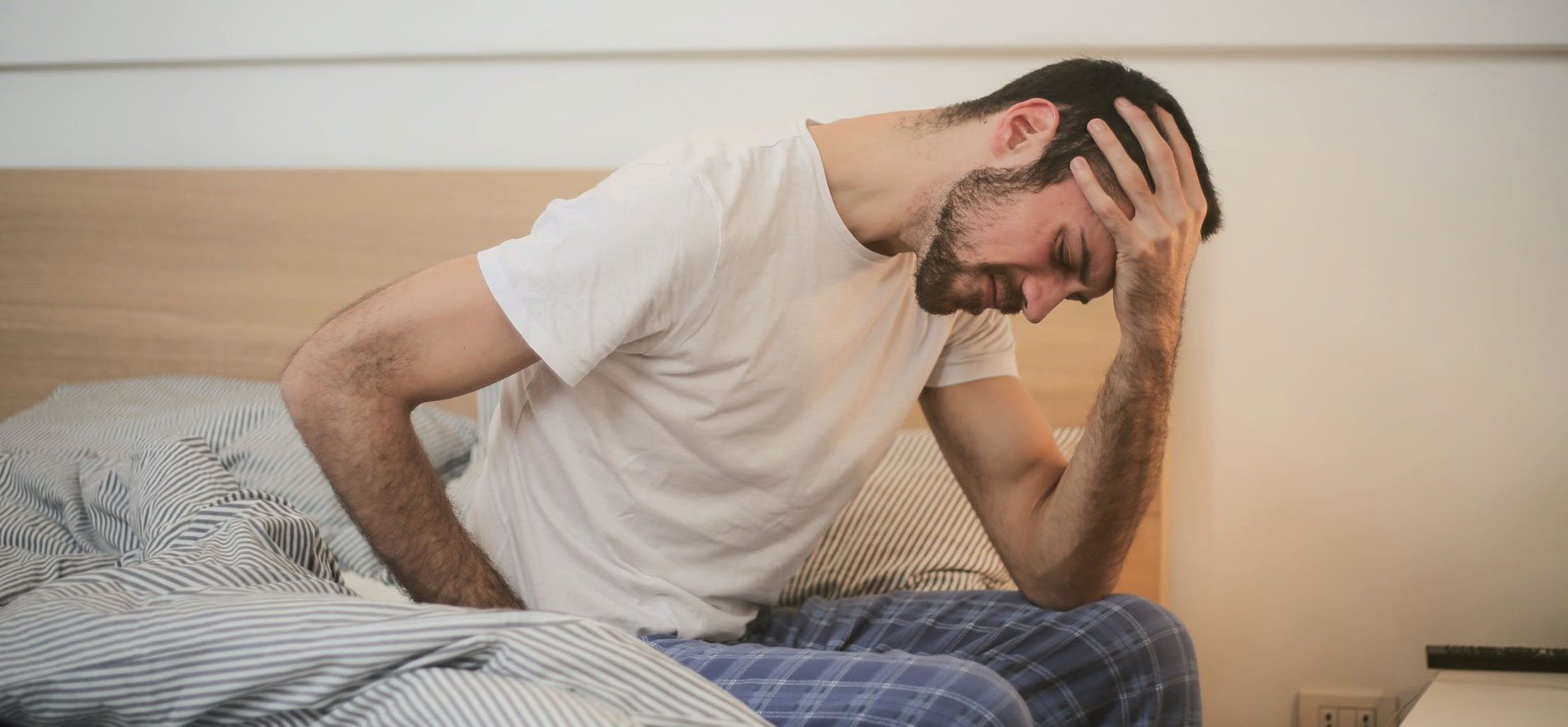 young man sitting in bed, holding head in hand because of shoulder discomfort
